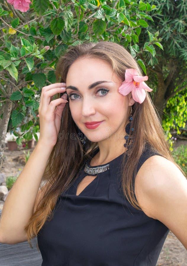 Ritratto di bella giovane donna castana con un fiore dietro il suo orecchio, in un giardino di fioritura Con un bello sorriso immagine stock libera da diritti