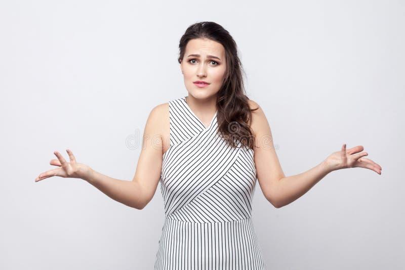 Ritratto di bella giovane donna castana confusa con trucco e la condizione a strisce del vestito e l'esame della macchina fotogra fotografia stock libera da diritti