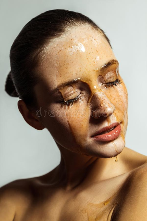 Ritratto di bella giovane donna castana felice con le lentiggini ed il miele sul fronte con gli occhi chiusi ed il fronte di feli immagine stock