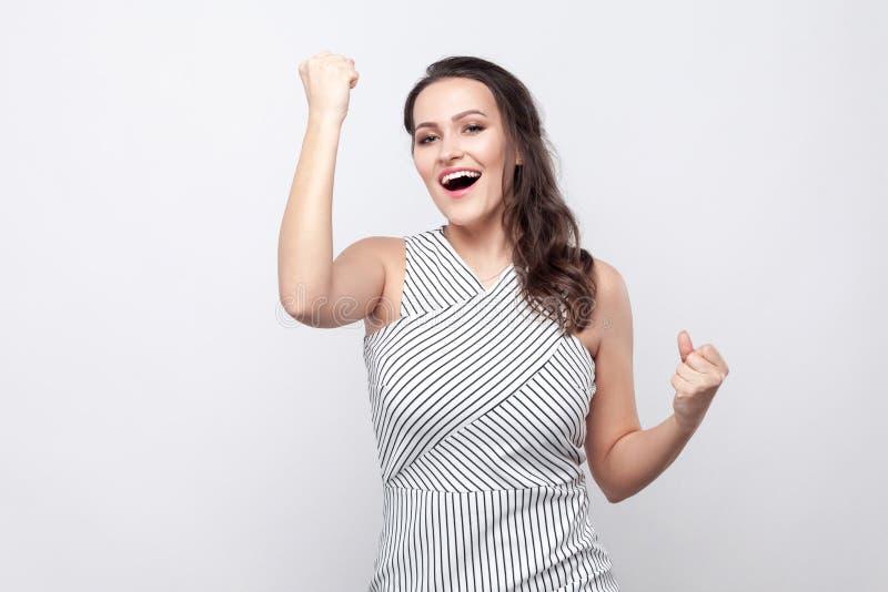 Ritratto di bella giovane donna castana felice con trucco e la condizione a strisce del vestito e l'esame della macchina fotograf immagini stock