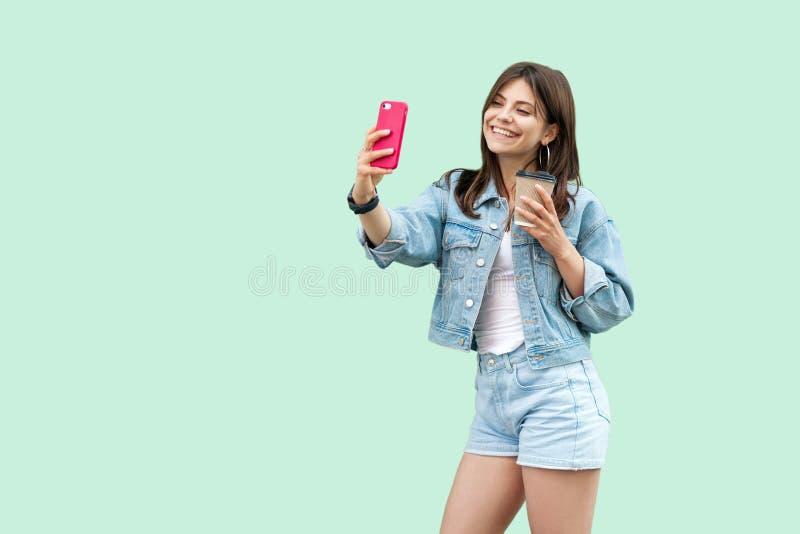 Ritratto di bella giovane donna castana felice nella condizione casuale e nella tenuta di stile del denim smartphone mobile e del fotografie stock libere da diritti