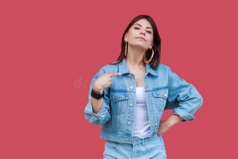 Ritratto di bella giovane donna castana fiera con trucco nella condizione di stile casuale del denim, indicantesi ed esaminante fotografie stock libere da diritti