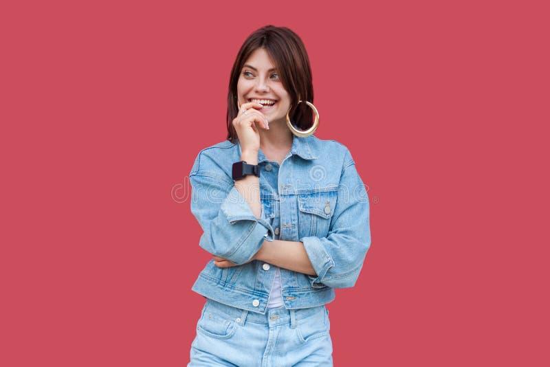 Ritratto di bella giovane donna castana vaga ottimista con trucco nella condizione di stile casuale del denim, sorridere a trenta immagini stock