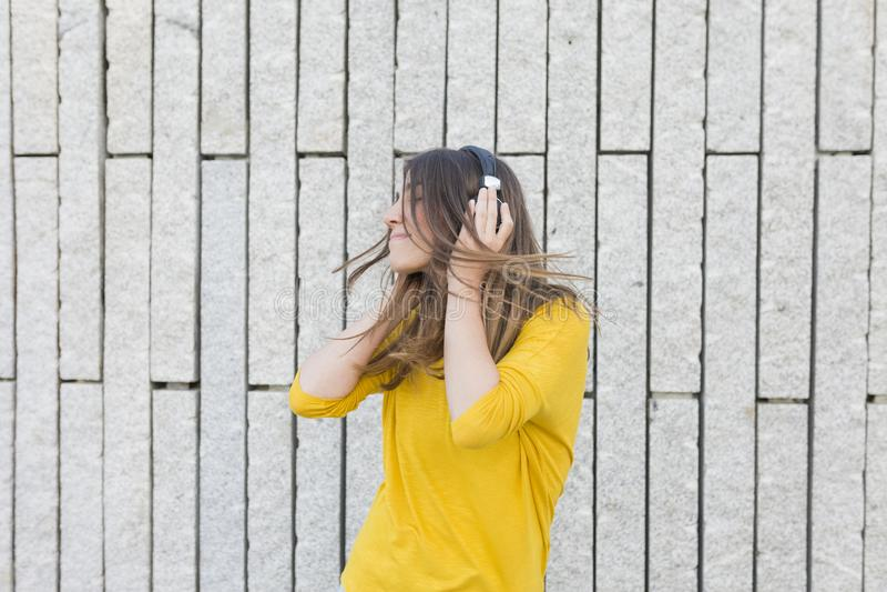 Ritratto di bella giovane donna che ascolta la musica sulle cuffie Sta ballando, saltando e sorridendo Abbigliamento casual fotografie stock libere da diritti