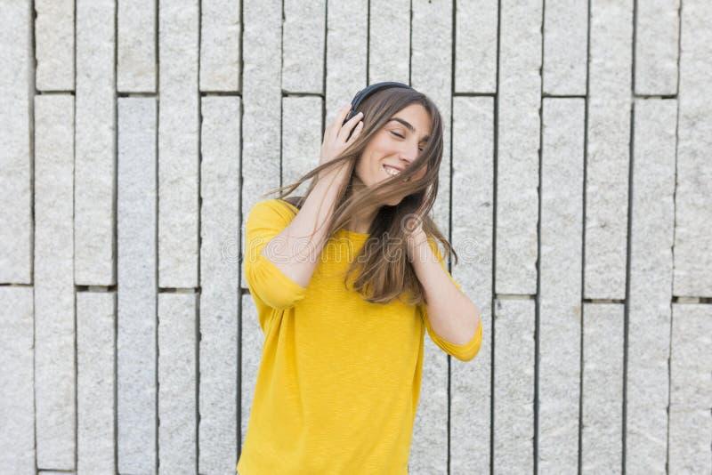 Ritratto di bella giovane donna che ascolta la musica sulle cuffie Sta ballando, saltando e sorridendo Abbigliamento casual fotografia stock