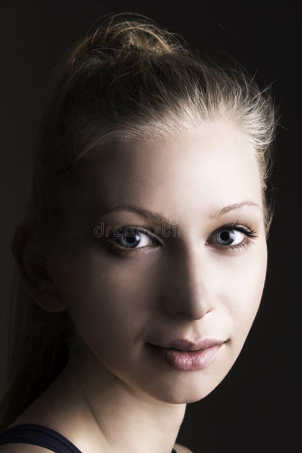 Ritratto di bella giovane donna che esamina macchina fotografica fotografia stock