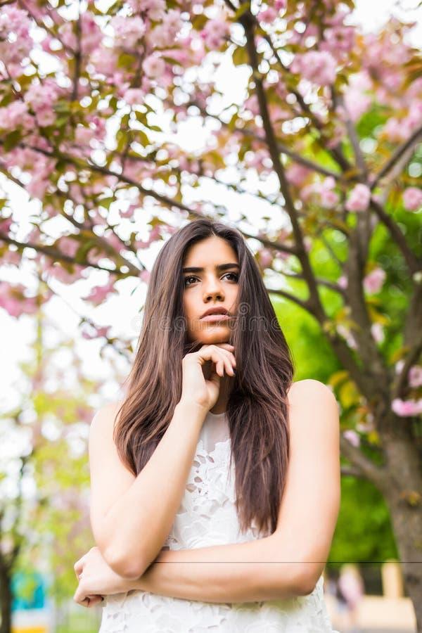 Ritratto di bella giovane donna che gode del giorno soleggiato in parco durante la stagione del fiore di ciliegia un giorno di mo fotografia stock libera da diritti
