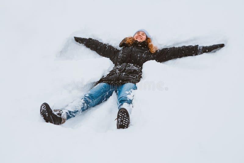 Ritratto di bella giovane donna che indica su un lago congelato della neve che la muove armi e gambe su e giù creare un angelo f  immagini stock libere da diritti