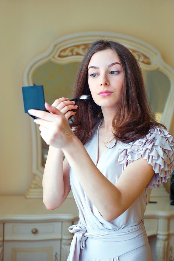 Ritratto di bella giovane donna che mette sul trucco immagine stock