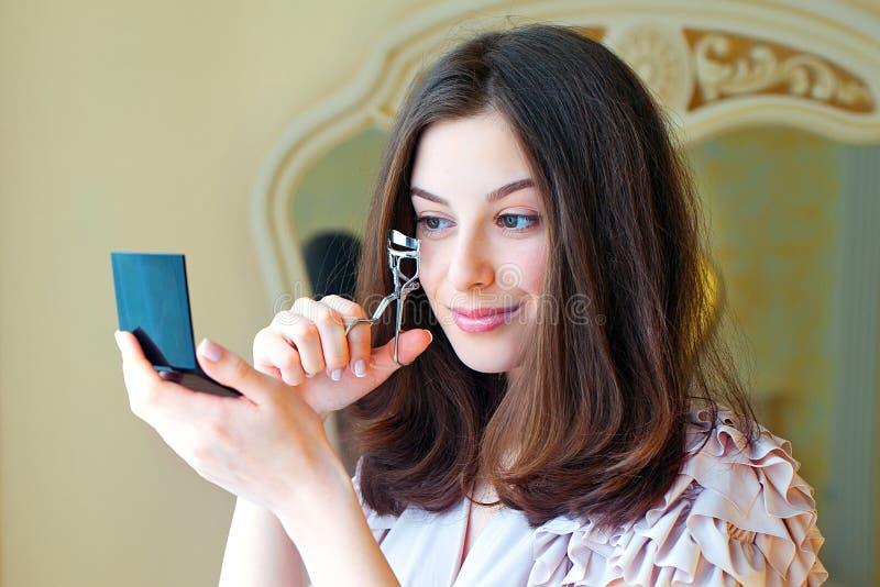 Ritratto di bella giovane donna che per mezzo del bigodino del ciglio fotografie stock libere da diritti