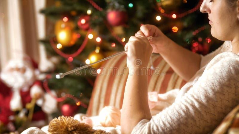 Ritratto di bella giovane donna che si siede in poltrona accanto all'albero di Natale ed a tricottare fotografia stock libera da diritti