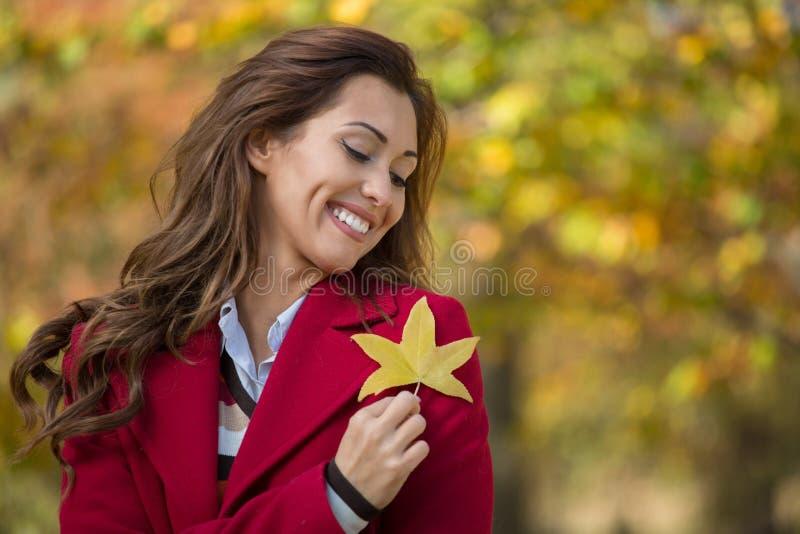 Ritratto di bella giovane donna che tiene una foglia di autunno e una s immagine stock