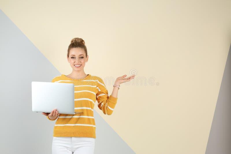 Ritratto di bella giovane donna con il computer portatile sul fondo di colore immagini stock