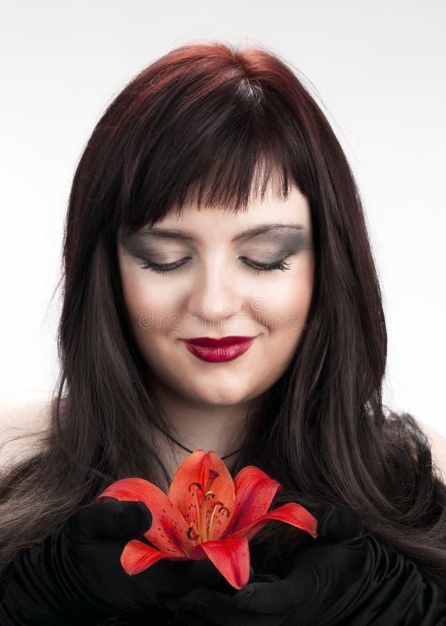 Ritratto di bella giovane donna con il giglio rosso fotografia stock libera da diritti