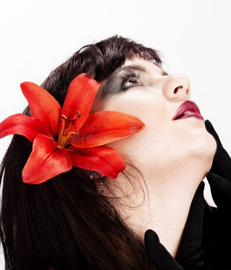 Ritratto di bella giovane donna con il giglio rosso fotografia stock