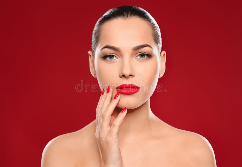 Ritratto di bella giovane donna con il manicure luminoso sul fondo di colore fotografia stock