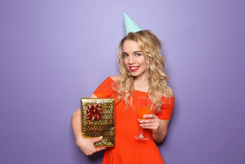 Ritratto di bella giovane donna con il regalo di compleanno ed il vetro di champagne sul fondo di colore immagini stock libere da diritti