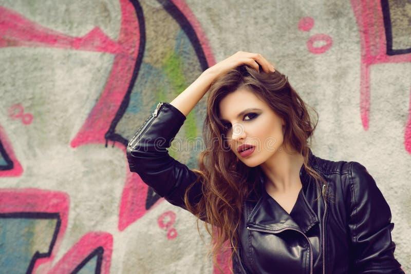Ritratto di bella giovane donna con la posa marrone ondulata dei capelli all'aperto, sopra il fondo dei graffiti modificato immagini stock libere da diritti
