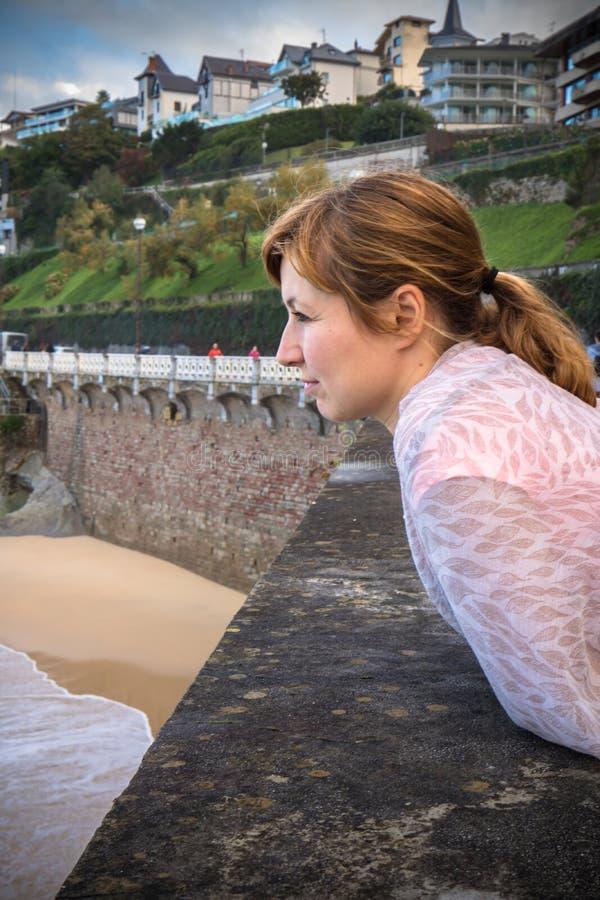 Ritratto di bella giovane donna dai capelli rossi che si appoggia la parete, osservando le onde ed i surfisti sulla riva della co fotografia stock