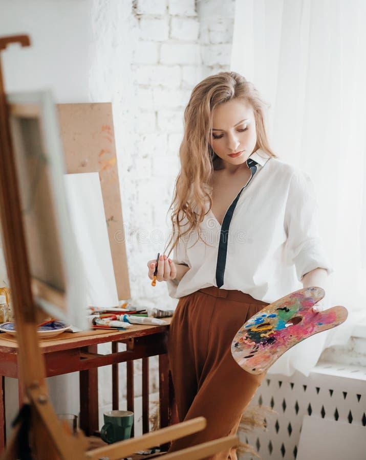 Ritratto di bella giovane donna dell'artista con le spazzole e le pitture fotografia stock libera da diritti