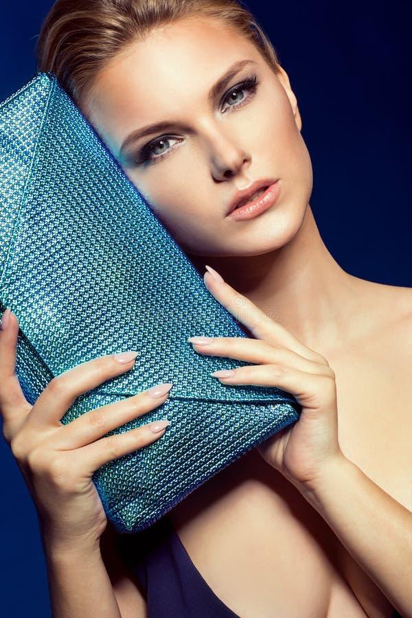 Ritratto di bella giovane donna di affari sul blu con la borsa fotografia stock libera da diritti