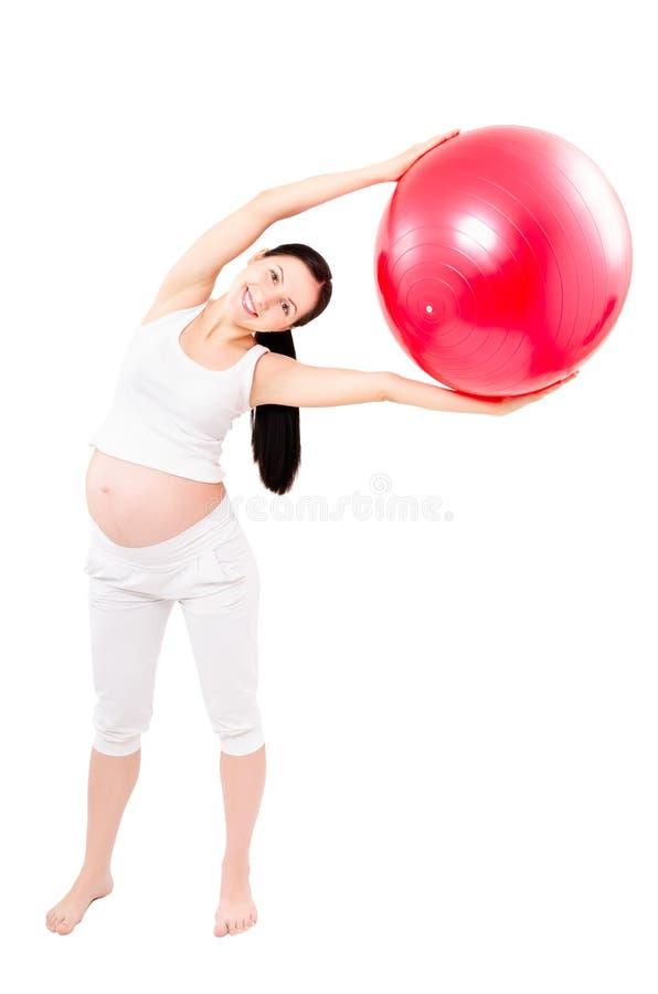 Ritratto di bella giovane donna incinta che esegue gli esercizi con fitball fotografia stock libera da diritti