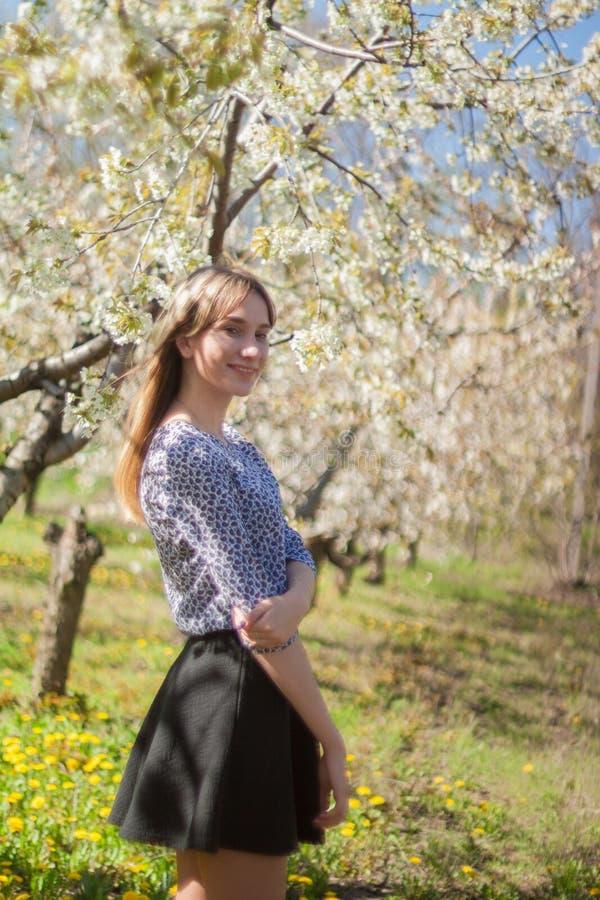 Ritratto di bella giovane donna nel parco di fioritura di melo un giorno soleggiato Ragazza felice sorridente della ragazza Conce fotografie stock