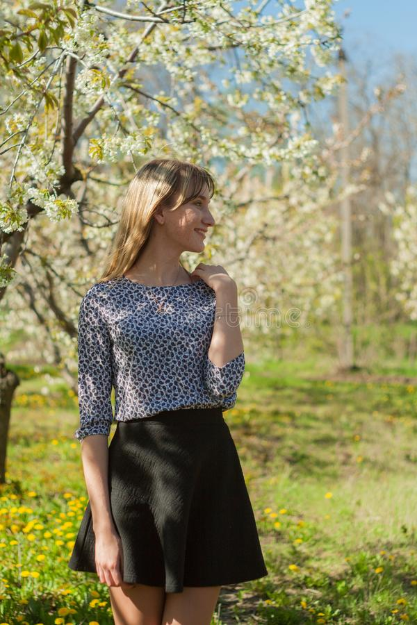 Ritratto di bella giovane donna nel parco di fioritura di melo un giorno soleggiato Ragazza felice sorridente della ragazza felic fotografia stock libera da diritti