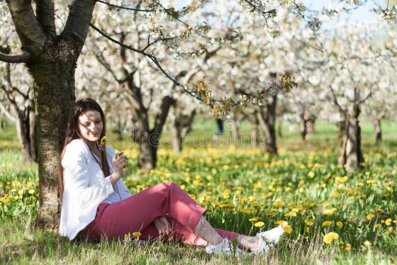 Ritratto di bella giovane donna nel parco di fioritura di melo un giorno soleggiato Ragazza felice sorridente della ragazza felic immagini stock libere da diritti