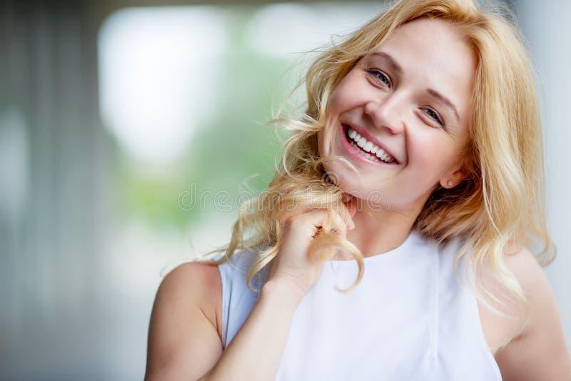 Ritratto di bella giovane donna sorridente che tocca i suoi capelli immagini stock