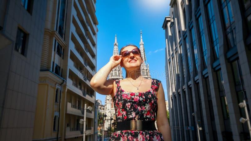 Ritratto di bella giovane donna sorridente in occhiali da sole che posano contro la costruzione moderna e la vecchia cattedrale c fotografie stock libere da diritti