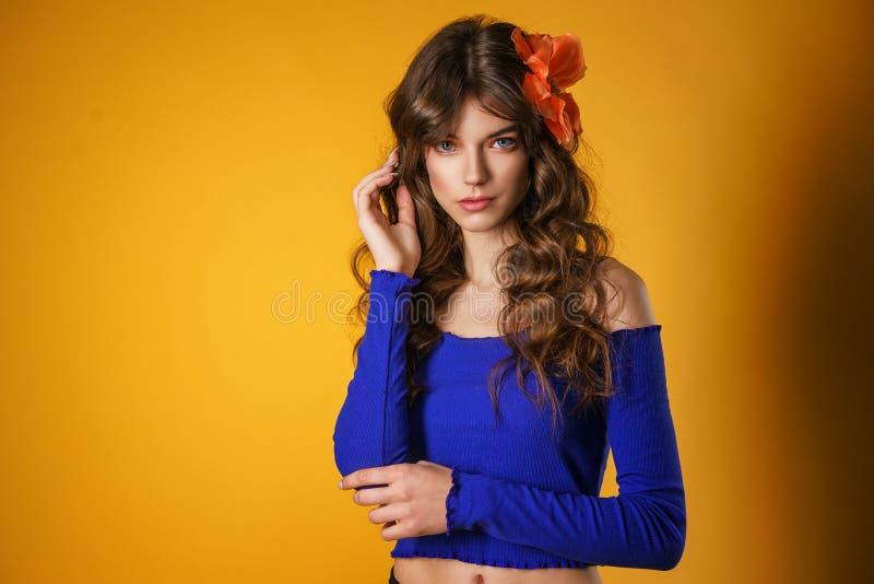 Ritratto di bella giovane donna su un fondo giallo, bello fiore in suoi capelli, trucco naturale delicato fotografia stock libera da diritti
