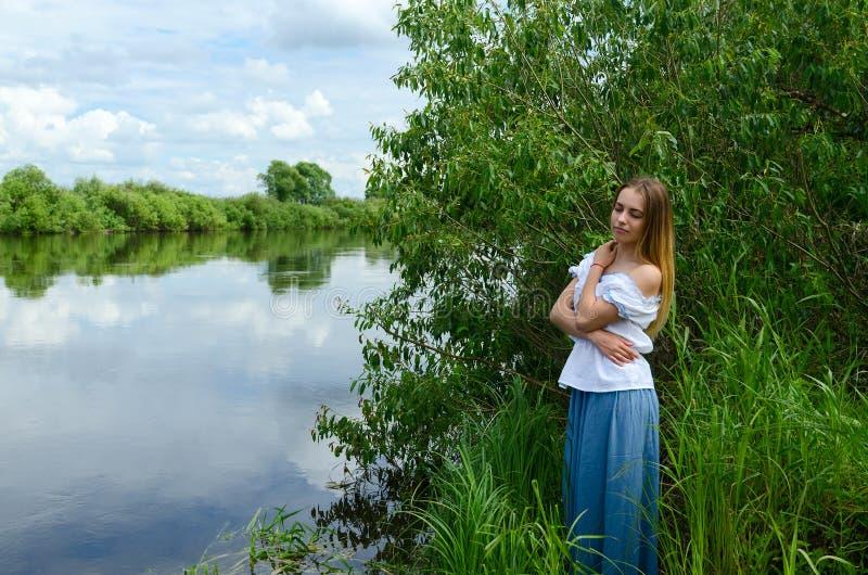 Ritratto di bella giovane donna sulla sponda del fiume immagini stock