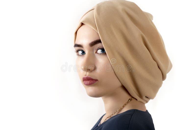 Ritratto di bella giovane donna in un turbante musulmano, sopra fondo bianco immagini stock libere da diritti