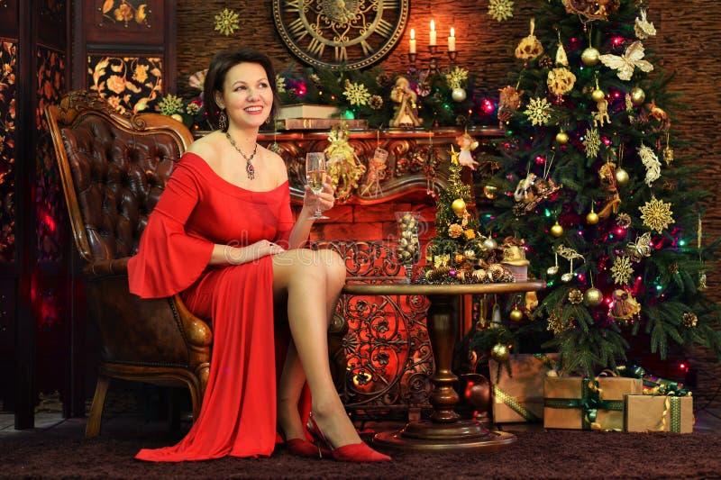 Ritratto di bella giovane donna in vestito rosso che tiene vetro di fotografie stock libere da diritti