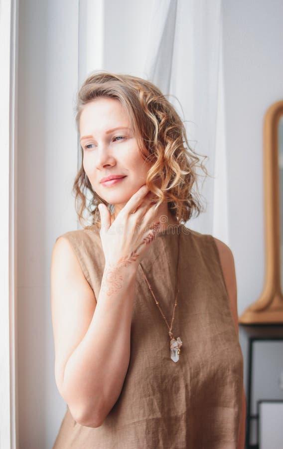 Ritratto di bella giovane donna in vestito di tela vicino alla finestra, concetto naturale di bellezza di eco fotografia stock