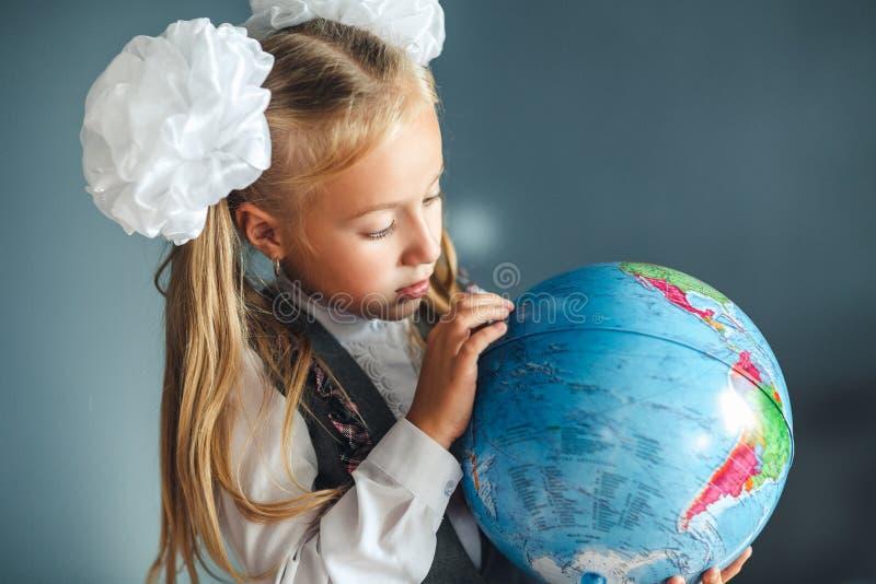 Ritratto di bella giovane ragazza della scolara che esplora il globo Giorno di conoscenza Inizio dell'anno scolastico studiare fotografia stock libera da diritti