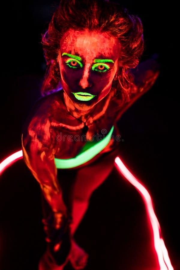 Ritratto di bella giovane ragazza sexy con pittura ultravioletta sul suo corpo Donna graziosa con bodyart d'ardore nel nero immagine stock