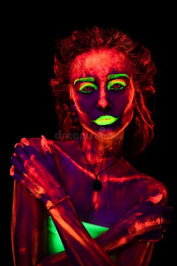 Ritratto di bella giovane ragazza sexy con pittura ultravioletta sul suo corpo Donna graziosa con bodyart d'ardore nel nero immagini stock
