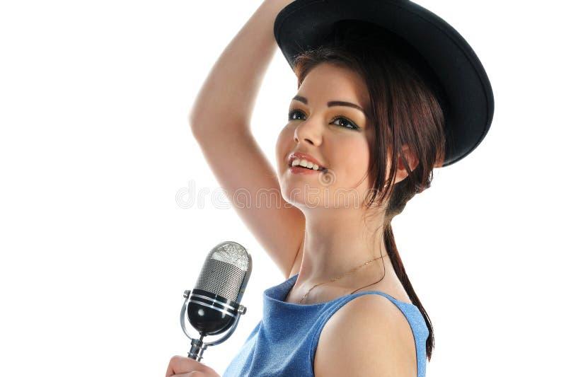 Ritratto di bella giovane ragazza sorridente in un cappello con un retro microfono su bianco fotografie stock libere da diritti