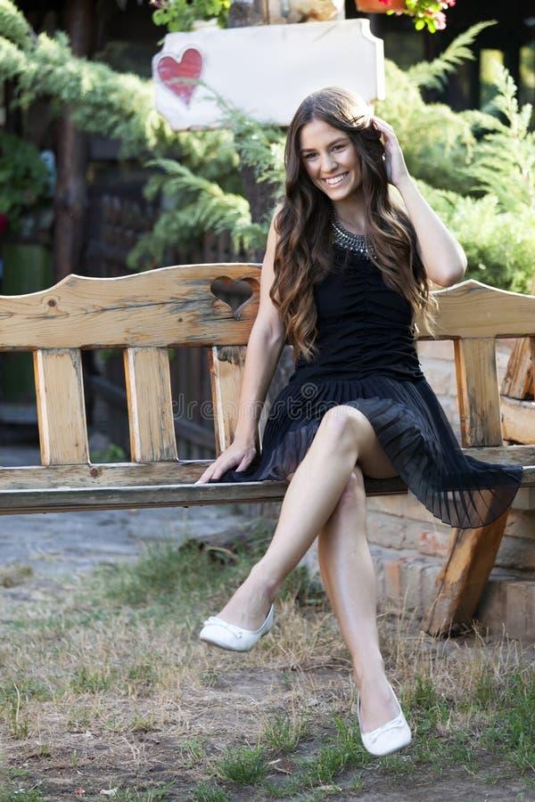 Ritratto di bella giovane ragazza sorridente in un vestito mentre sitt fotografie stock libere da diritti