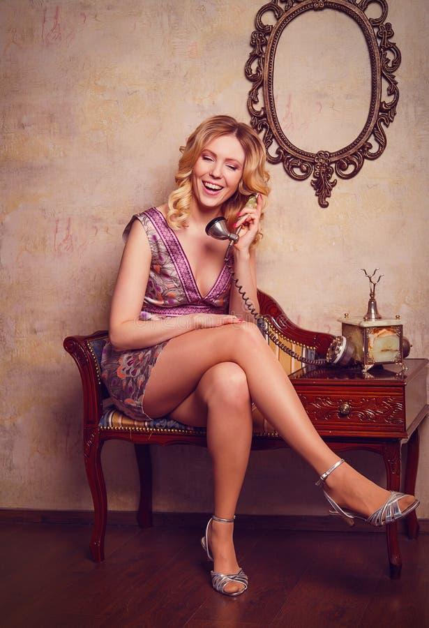 Ritratto di bella giovane signora sensuale con il telefono alla moda fotografia stock libera da diritti