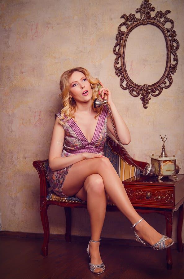 Ritratto di bella giovane signora sensuale con il telefono alla moda fotografia stock