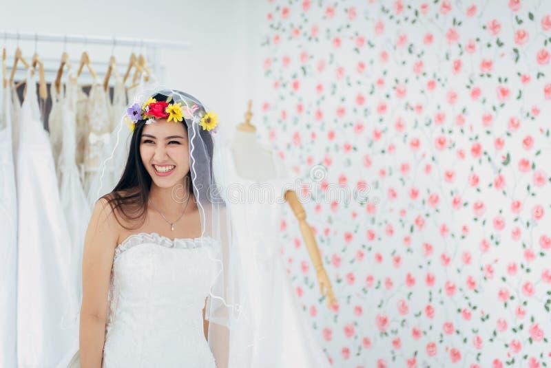 Ritratto di bella giovane sposa asiatica delle donne in vestito bianco allegro e divertente, di cerimonia nel giorno delle nozze, fotografia stock