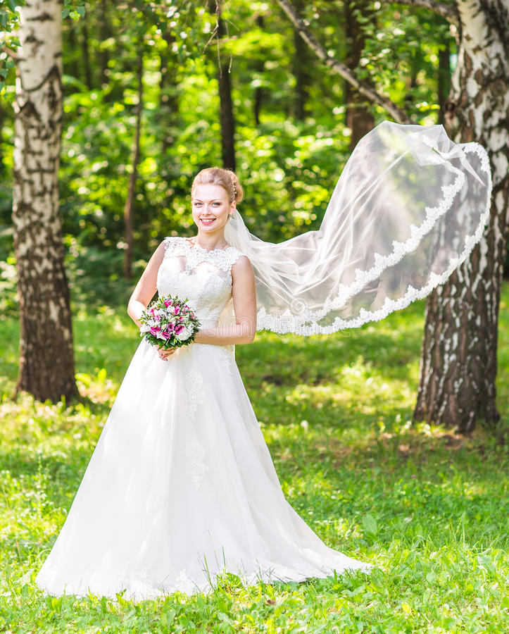 Ritratto di bella giovane sposa in vestito bianco elegante con il velo lungo all'aperto fotografie stock libere da diritti