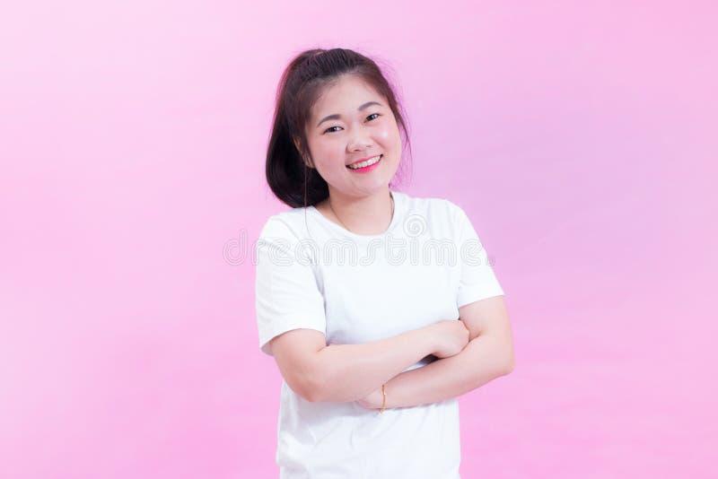 Ritratto di bella giovane usura asiatica dei capelli neri della donna una maglietta bianca Le armi hanno attraversato e sorriso c fotografia stock