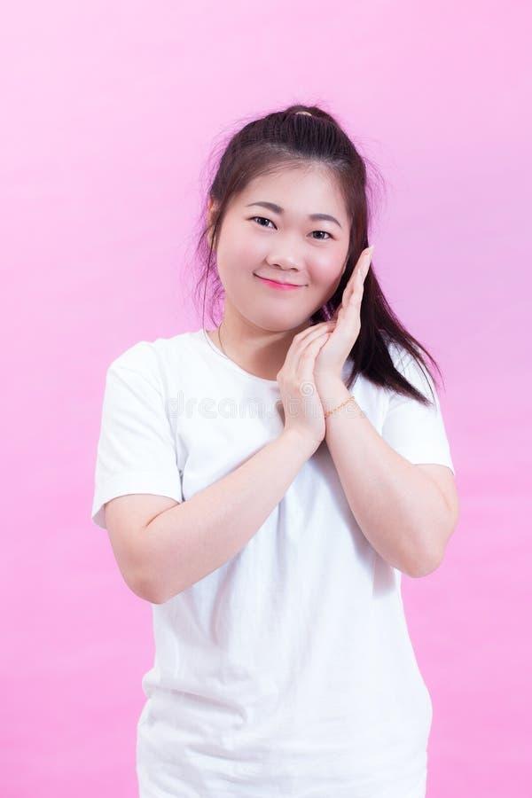 Ritratto di bella giovane usura asiatica dei capelli neri della donna una maglietta bianca Sfrega le sue palme vicino al fronte s fotografie stock