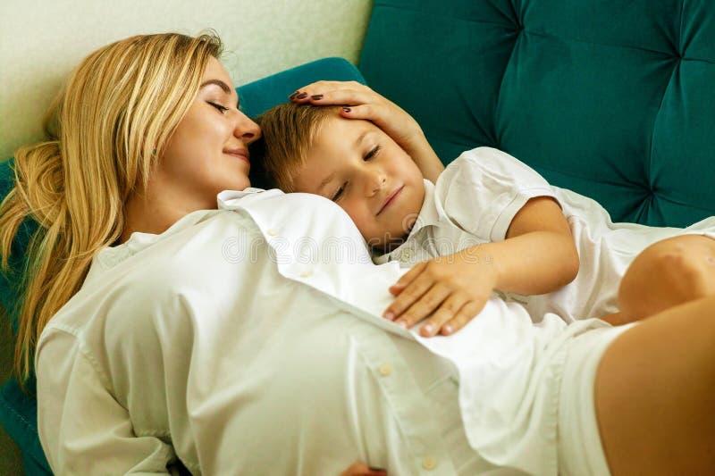 Ritratto di bella madre incinta, abbracciando con l'amore e la tenerezza il suo bambino prezioso a casa immagine stock