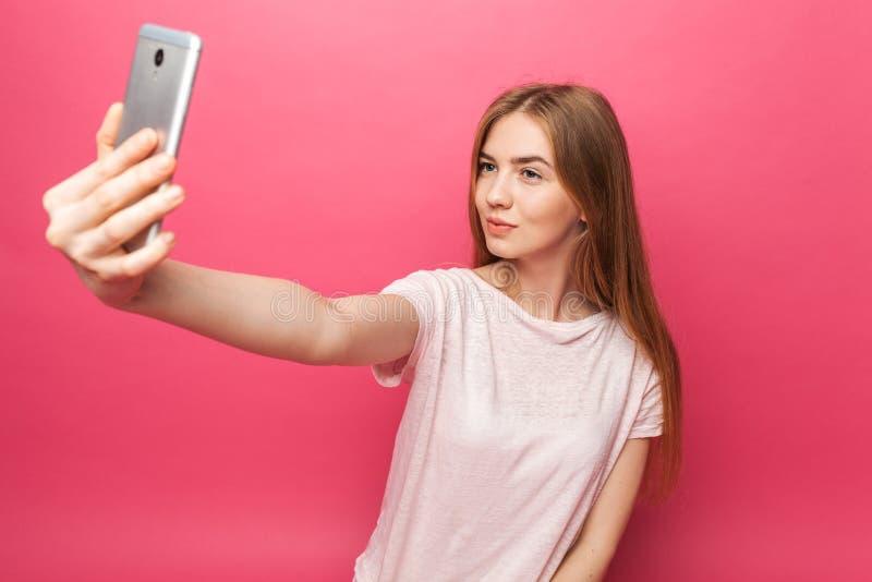 Ritratto di bella ragazza allegra, fotografato, prendendo selfie, esaminante il telefono, abbastanza divertente, su backgroun ros immagine stock libera da diritti