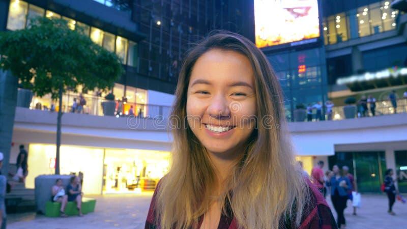 Ritratto di bella ragazza asiatica orientale sorridente Nei precedenti sono le luci vaghe di grande supermercato fotografia stock libera da diritti